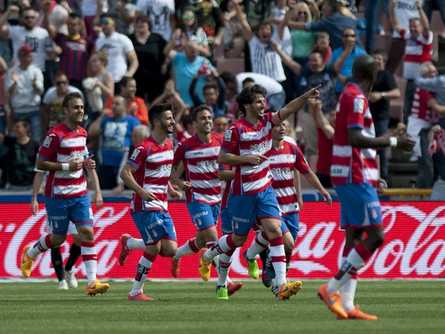 Granada's defender Diego Mainz celebrates with teammates after scoring a goal during the Spanish league football match Granada FC v Sevilla FC at Nuevo Los Carmenes stadium in Granada on April 19, 2015
