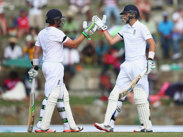 Ian Bell and Joe Root of England bring up their 150 run partnership during day one of the 1st Test match between West Indies and England at the Sir Vivian Richards Stadium on April 13, 2015