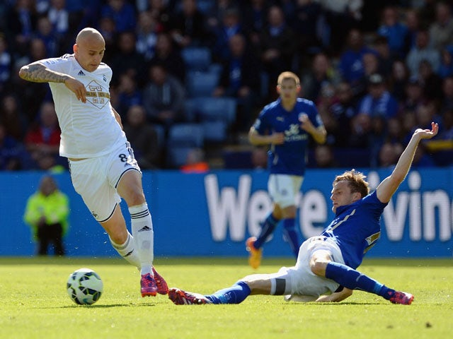Marc Albrighton of Leicester City tackles Jonjo Shelvey of Swansea during the Barclays Premier League match between Leicester City and Swansea City at The King Power Stadium on April 18, 2015