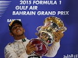 Mercedes AMG Petronas British driver Lewis Hamilton celebrates with his trophy on the podium after winning the Formula One Bahrain Grand Prix at the Sakhir circuit in the desert south of the Bahraini capital, Manama, on April 19, 2015