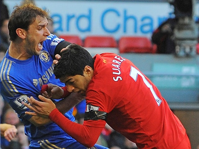Liverpool's Uruguayan striker Luis Suarez clashes with Chelsea's Serbian defender Branislav Ivanovic after appearing to bite the Chelsea player during the English Premier League football match between Liverpool and Chelsea at the Anfield stadium in Liverp