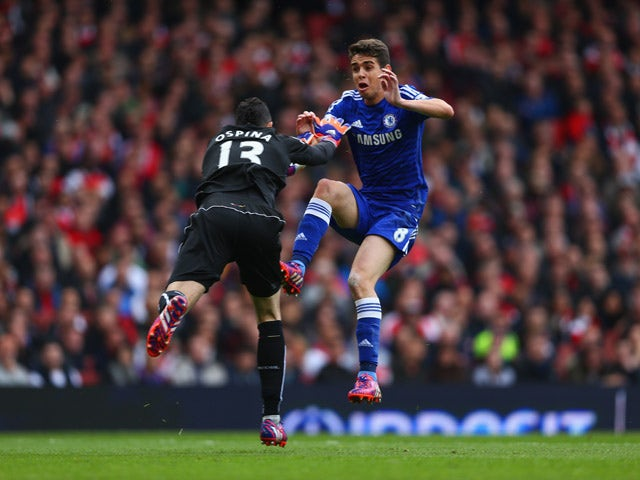 David Ospina of Arsenal and Oscar of Chelsea collide during the Barclays Premier League match between Arsenal and Chelsea at Emirates Stadium on April 26, 2015