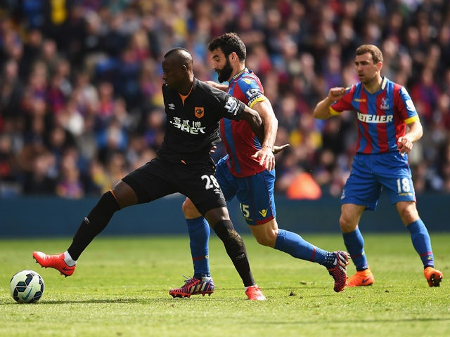 Dame N'Doye of Hull City is challenged by Mile Jedinak of Crystal Palace during the Barclays Premier League match between Crystal Palace and Hull City at Selhurst Park on April 25, 2015