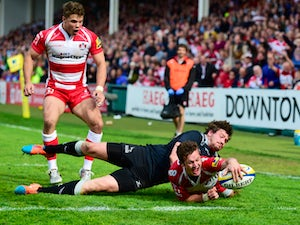 Gloucester player Billy Burns scores the winning try despite the attentions of Adam Powell during the Aviva Premiership match between Gloucester Rugby and Newcastle Falcons at Kingsholm Stadium on April 25, 2015