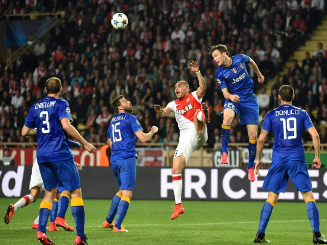 Juventus' defender from Switzerland Stephan Lichtsteiner and Monaco's French defender Layvin Kurzawa go for a header during the UEFA Champions League quarter final second leg football match AS Monaco vs Juventus FC on April 22, 2015