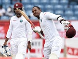 West Indies batsman Marlon Samuels celebrates after scoring his century as team captain/wicketkeeper Denesh Ramdin looks on during day two of the second Test match between West Indies and England at the Grenada National Stadium in Saint George's on April