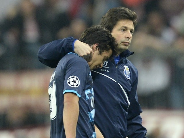 Porto's Spanish midfielder Oliver Torres (L) and a staff member react after the UEFA Champions League second-leg quarter-final football match Bayern Munich v FC Porto in Munich, southern Germany on April 21, 2015