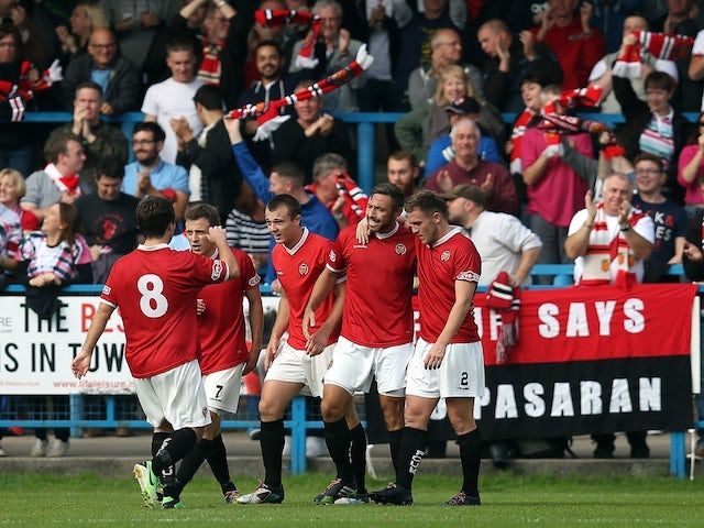 Tom Greaves of FC United Of Manchester is congratulated by his team-mates after scoring the opening goal during the FA Cup Qualifying First Round match between FC United Of Manchester and Prescot Cables on September 14, 2014
