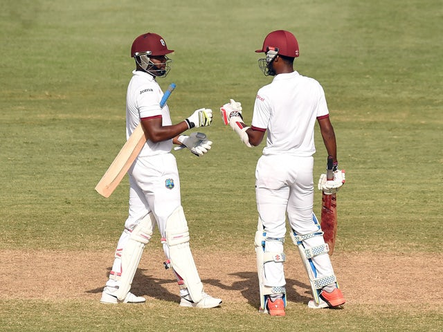West Indies batsmen Kraigg Brathwaite and Darren Bravo confer during day four of the second Test cricket match between the West Indies and England at the Grenada National Stadium in Saint George's on April 24, 2015