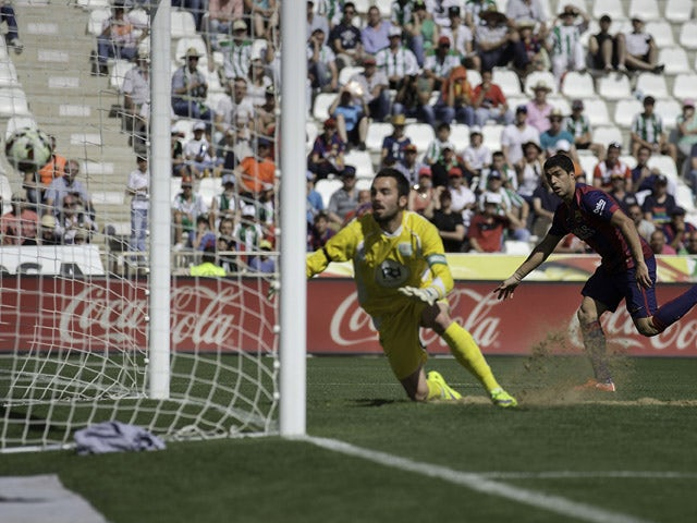 Luis Suarez of FC Barcelona scores their fourth goal past goalkeeper Juan Carlos Martin of Cordoba CF during the La Liga match between Cordoba CF and Barcelona FC at El Arcangel stadium on May 2, 2015