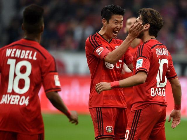 Leverkusen's midfielder Hakan Calhanoglu celebrates scoring with South Korean striker Heung Min Son during the German first division Bundesliga football match between Bayer 04 Leverkusen and FC Bayern Munich at the BayArena in Leverkusen, western Germany,