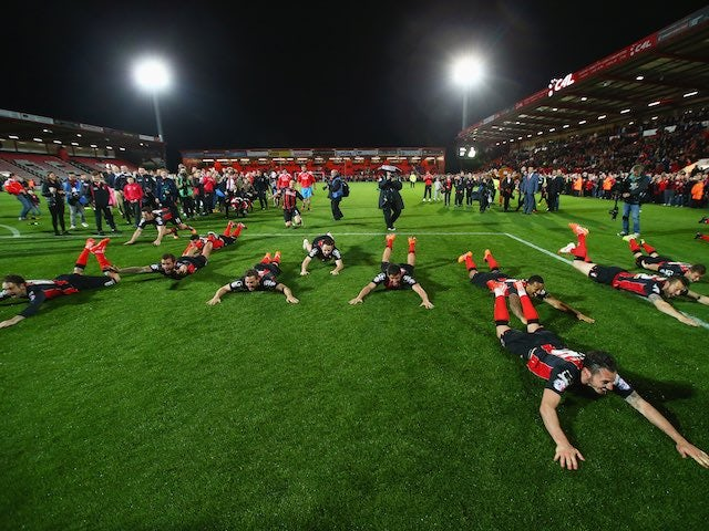 Bournemouth players celebrate after their 3-0 win against Bolton Wanderers which effectively sealed promotion to the Premier League on April 27, 2015