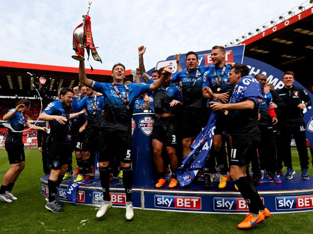 Tommy Elphick of Bournemouth lifts the trophy while Bournemouth players celebrate winning the Championship after the Sky Bet Championship match between Charlton Athletic and AFC Bournemouth at The Valley on May 2, 2015