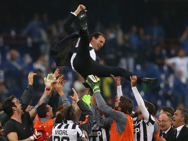 Juventus' players celebrate with their coach Massimiliano Allegri after winning the 'Scudetto' at the end of the Italian Serie A football match Sampdoria Vs Juventus on May 2, 2015