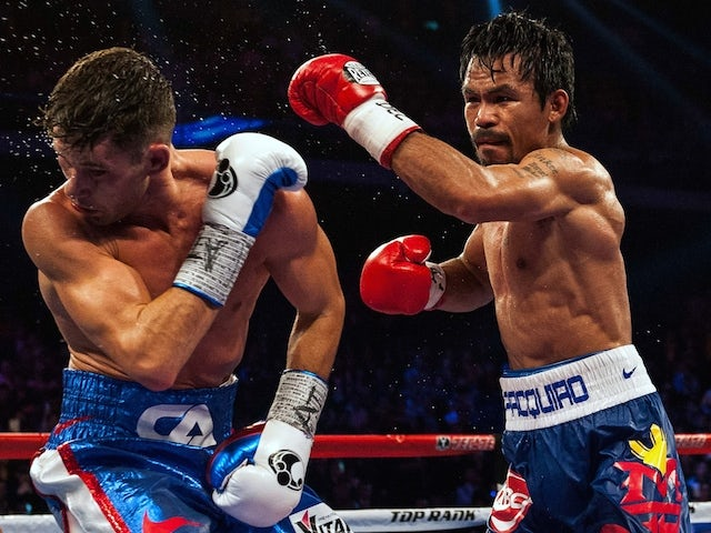 Manny Pacquiao of the Philippines (R) fights against Chris Algieri of the US during their World Boxing Organization welterweight title bout at the Cotai Arena in Macau on November 23, 2014