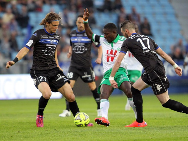 Saint- Etienne's Ivorian forward Max-Alain Gradel vies Bastia's French midfielder Guillaume Gillet and Bastia's French defender Mathieu Peybernes (R) during the French L1 football match between Bastia and Saint-Etienne on May 2, 2015