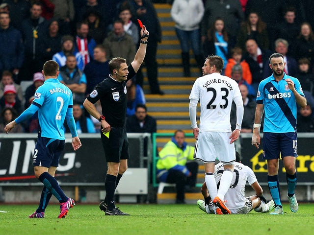 Marc Wilson of Stoke City is shown the red card by referee Craig Pawson during the Barclays Premier League match between Swansea City and Stoke City at Liberty Stadium on May 2, 2015