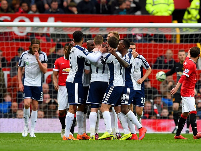Chris Brunt of West Brom celebrates with team-mates after taking a free-kick which was deflected off Jonas Olsson of West Brom to score the opening goal during the Barclays Premier League match between Manchester United and West Bromwich Albion at Old Tra