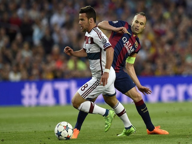 Barcelona's midfielder Andres Iniesta (R) vies with Bayern Munich's Spanish defender Juan Bernat (L) during the UEFA Champions League football match FC Barcelona vs FC Bayern Muenchen at the Camp Nou stadium in Barcelona on May 6, 2015