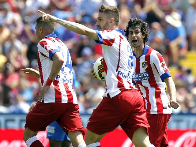 Atletico Madrid's Brazilian defender Guilherme Siqueira celebrates with teammates after scoring a goal during the Spanish league football match Levante UD vs Club Atletico de Madrid at the Ciutat de Valencia stadium in Valencia on May 10, 2015