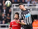 Newcastle United's French striker Emmanuel Riviere (R) challenges West Bromwich Albion's Argentinian midfielder Claudio Yacob (L) during the English Premier League football match between Newcastle United and West Bromwich Albion at St James Park, Newcastl