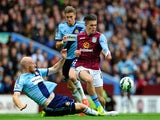 Jack Grealish of Aston Villa is tackled by James Collins of West Ham United during the Barclays Premier League match between Aston Villa and West Ham United at Villa Park on May 9, 2015