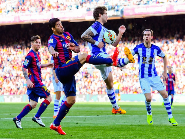 Luis Suarez of FC Barcelona competes for the ball with Inigo Martinez of Real Sociedad de Futbol during the La Liga match between FC Barcelona and Real Sociedad de Futbol at Camp Nou on May 9, 2015