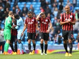 A dejected Joey Barton of QPR and teammates react following their team's relegation during the Barclays Premier League match between Manchester City and Queens Park Rangers at the Etihad Stadium on May 10, 2015