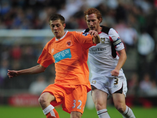 Tom Barkhuizen of Blackpool shields the ball from Dean Lewington of MK Dons during the Carling Cup 2nd Round match between MK Dons and Blackpool at Stadium MK on August 24, 2010