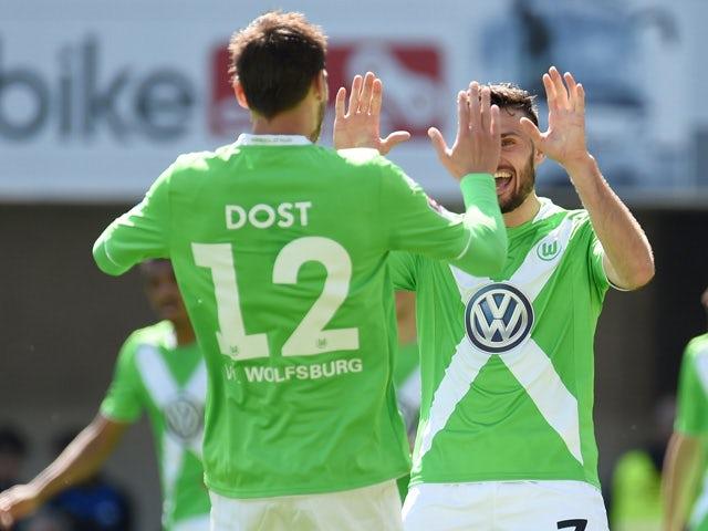 Wolfsburg's midfielder Daniel Caligiuri and Wolfsburg's Dutch striker Bas Dost celebrate during the German first division Bundesliga football match of SC Paderborn 07 vs VfL Wolfsburg in Paderborn, western Germany on May 10, 2015