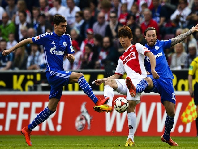 Cologne's Japanese striker Yuya Osako (C) vies for the ball with Schalke's midfielder Marco Hoeger (R) during the German first division Bundesliga football match of FC Cologne vs FC Schalke 04 in Cologne, western Germany on May 10, 2015