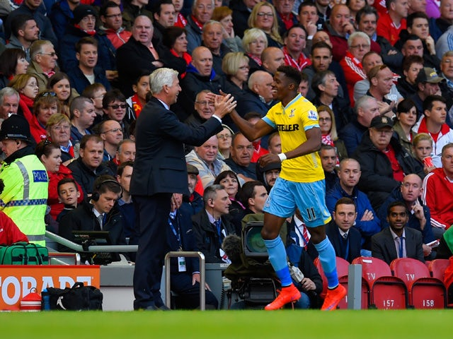 Manager Alan Pardew of Crystal Palace congratulates Wilfried Zaha of Crystal Palace on scoring their second goal during the Barclays Premier League match between Liverpool and Crystal Palace at Anfield on May 16, 2015