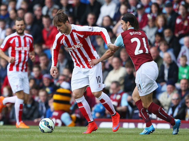Marko Arnautovic of Stoke City and George Boyd of Burnley compete for the ball during the Barclays Premier League match between Burnley and Stoke City at Turf Moor on May 16, 2015