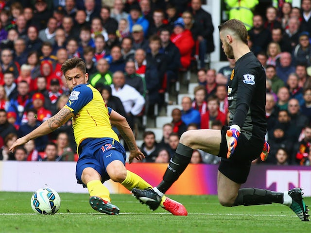 Olivier Giroud of Arsenal is faced by David De Gea of Manchester United as he misses a chance during the Barclays Premier League match between Manchester United and Arsenal at Old Trafford on May 17, 2015