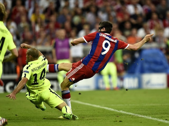 Bayern Munich's Polish forward Robert Lewandowski (R) shoots to score during the UEFA Champions League football match semi final FC Bayern Munich vs FC Barcelona in Munich on May 12, 2015