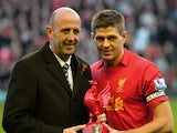 Liverpool's English midfielder Steven Gerrard receives an award from former captain Gary McAllister to mark his 600th appearance for the club before the English Premier League football match between Liverpool and Newcastle United at Anfield in Liverpool,