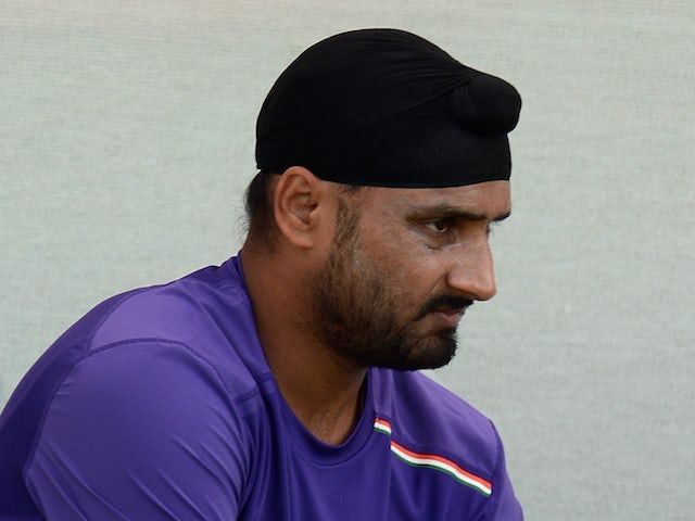 Indian cricketer Harbhajan Singh puts on his pads as he prepares to bat during a training session at The Sardar Patel Stadium at Motera in Ahmedabad on November 14, 2012
