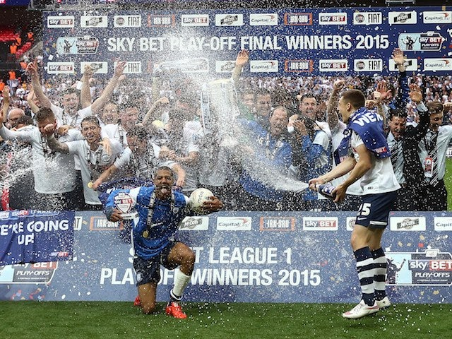 Preston North End players take a spray to the face after winning promotion to the Championship on May 24, 2015