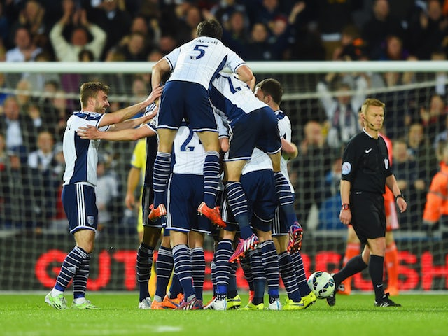 Chris Brunt of West Bromwich Albion (obscured) is mobbed by team mates in celebration as he scores their third goal during the Barclays Premier League match between West Bromwich Albion and Chelsea at The Hawthorns on May 18, 2015