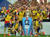 The Arsenal team pose with the trophy after winning the FA Cup final football match between Aston Villa and Arsenal at Wembley stadium in London on May 30, 2015