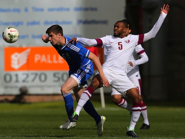 Qatar's Majdi Siddiq (R) vies for the ball with Northern Ireland`s Patrick McNair during the international friendly football match between Qatar and Northern Ireland at the Alexandra Stadium in Crewe on May 31, 2015