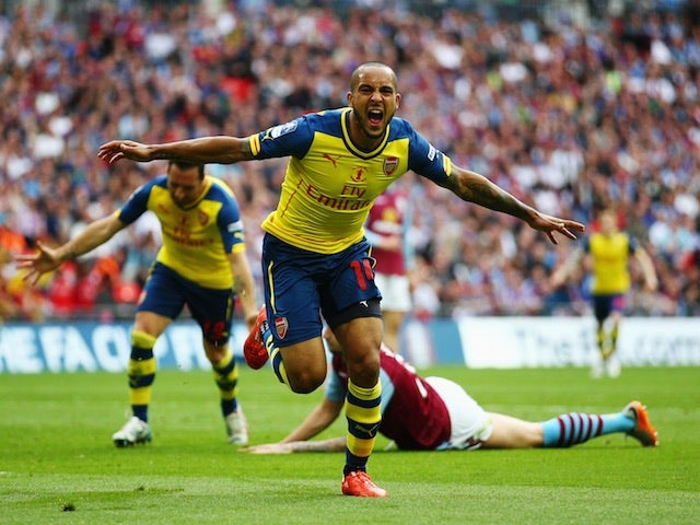 Theo Walcott wheels away in celebration after scoring the opening goal of the FA Cup final at Wembley between Arsenal and Aston Villa on May 30, 2015
