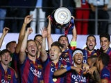 Xavi Hernandez of Barcelona lifts the trophy as he celebrates victory with team mates after the UEFA Champions League Final between Juventus and FC Barcelona at Olympiastadion on June 6, 2015