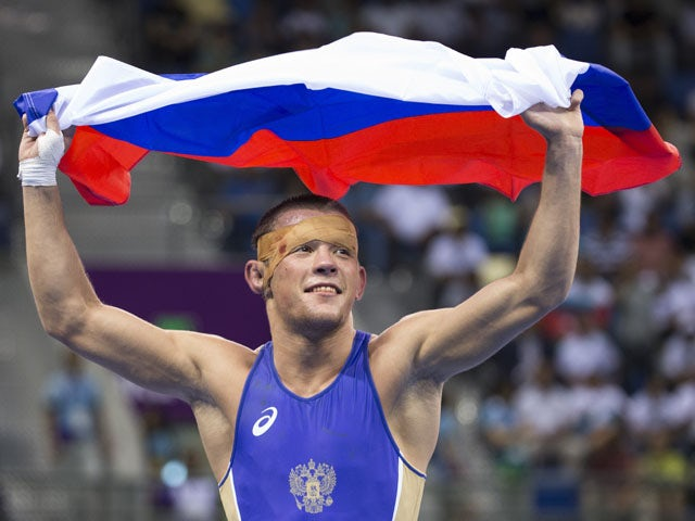 Russias Artem Surkov holds aloft his national flag following his bout against Armenias Migran Arutyunyan in the mens Greco-Roman 66kg wrestling Gold medal event of the 2015 European Games in Baku on June 14, 2015
