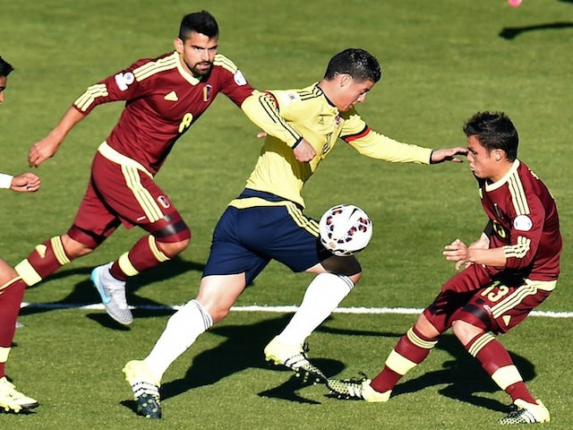 Colombia's midfielder James Rodriguez (C) is marked by Venezuela's Tomas Rincon and Luis Seijas (R) during their 2015 Copa America football championship match, in Rancagua, Chile, on June 14, 2015