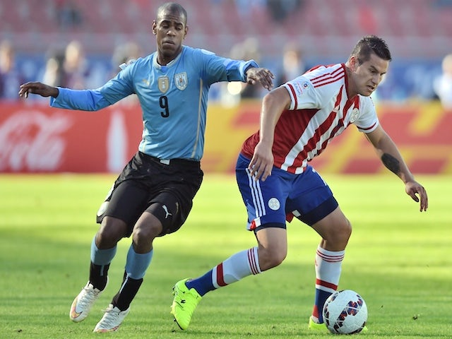Uruguay's forward Diego Rolan (L) and Paraguay's forward Raul Bobadilla vie for the ball during their 2015 Copa America football championship match, in La Serena, on June 20, 2015