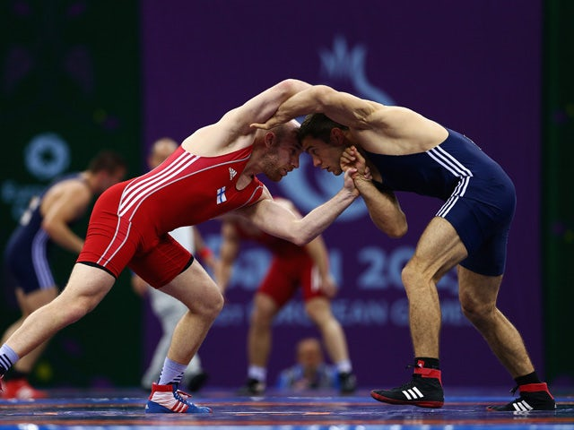 Ville Heino of Finland (red) and Piotr Ianulov of Macedonia (blue) compete in the Men's Wrestling 86kg Freestyle qualifications round during day six of the Baku 2015 European Games at the Heydar Aliyev Arena on June 18, 2015