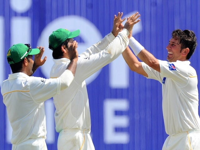 Pakistan cricketer Yasir Shah (R) and teammates celebrate the dismissal of Sri Lankan cricketer Rangana Herath during the final day of the opening Test match between Sri Lanka and Pakistan at the Galle International Cricket Stadium in Galle on June 21, 20