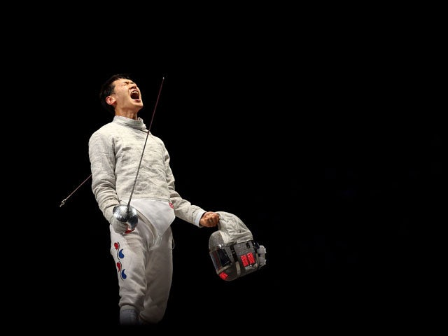 Bongil Gu of Korea celebrates against Tiberiu Dolniceanu of Romania during the Men's Sabre Team Fencing on Day 7 of the London 2012 Olympic Games at ExCeL on August 3, 2012