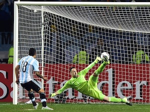 Argentina's forward Carlos Tevez (L) scores the winning penalty kcik past Colombia's goalkeeper David Ospina during the 2015 Copa America football championship quarterfinal match in Vina del Mar, Chile on June 26, 2015